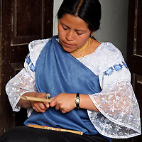 South America, Ecuador, Peguche. A young woman demonstrates the craft of making a panflute.