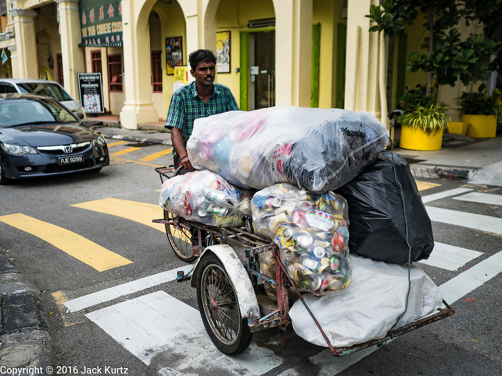 16 NOVEMBER 2016 - GEORGE TOWN, PENANG, MALAYSIA: A garbage scavenger and recycler steers his bike through traffic in George Town, Penang, Malaysia. George Town is a UNESCO World Heritage city and wrestles with maintaining its traditional lifestyle and mass tourism.       PHOTO BY JACK KURTZ