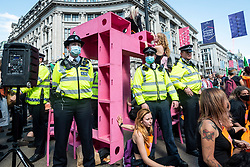 """© Licensed to London News Pictures. 25/08/2021. LONDON, UK.  Police officers and climate activists from Extinction Rebellion in Oxford Circus at a protest where people have glued themselves to a pink wooden structure.  The event is part of the 'Impossible Rebellion' protest to """"target the root cause of the climate and ecological crisis"""" and are ongoing for two weeks until the Government agrees to stop all new fossil fuel investments.  Photo credit: Stephen Chung/LNP"""