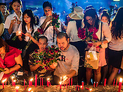 18 FEBRUARY 2016 - BANGKOK, THAILAND:  Men and women pray for love, holding nine red roses and sticks of incense, at the Trimurti Shrine in Bangkok. Every Thursday night, starting just after sunset and peaking at 21.30, hundreds of Bangkok single people, or couples seeking guidance and validation, come to the Trimurti Shrine at the northeast corner of Central World, a large Bangkok shopping mall, to pray to Lord Trimurti, who represents the trinity of Hindu gods - Brahma, Vishnu and Shiva. Worshippers normally bring an offering of red flowers, fruits, one red candle and nine incense sticks. It's believed that Lord Trimurti descends from the heavens at 21.30 on Thursday to listen to people's prayers. Although most Thais are Buddhists, several Hindu traditions have been incorporated into modern Thai Buddhism, including reverance for Trimurti.      PHOTO BY JACK KURTZ