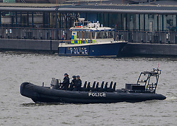 © Licensed to London News Pictures. 23/03/2017. London, UK. Police officers scan the river thames in a boat, the day after a lone terrorist killed 4 people and injured several more, in an attack using a car and a knife. The attacker managed to gain entry to the grounds of the Houses of Parliament, killing one police officer. Photo credit: Ben Cawthra/LNP