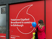 A Scots woman holding a blue balloon, talks on her phone outside a Vodafone shop advertising Gigafast Broadband, on Princes Street in Edinburgh, on 25th June 2019, in Edinburgh, Scotland.