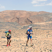 26 March 2007:  #394 Paolo Palermo of Italia (right) and #572 Munoz Gimenez of Spain (left) run across a very rocky plain during the second stage (21.7 miles) of the 22nd Marathon des Sables between Khermou and jebel El Otfal. The Marathon des Sables is a 6 days and 151 miles endurance race with food self sufficiency across the Sahara Desert in Morocco. Each participant must carry his, or her, own backpack containing food, sleeping gear and other material.