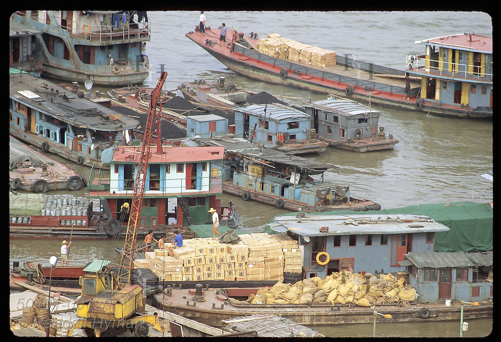 Barges filled with goods bustle with activity as they dock at wharf on Huangpu River; Shanghai China