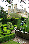 A view of Bourton House from the stunning knot garden. In the centre of the garden is a huge antique basket-weave design pond in raised Cotswold stone. The maze-like beds of the knot garden, precision-cut from box (Buxus sempervirens) are amazingly sharp and regular. At their corners are groups of pyramid topiaries. <br /> <br /> Date taken: 18 June 2010.