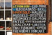 Sign - mussels, oysters, salmon, shrimp, lobster, cod, brill, sole, for sale at Gurneys Fish Shop, Burnham Market, Norfolk, UK
