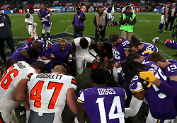 Players from the two teams kneel in a circle after the International Series NFL match at Twickenham, London.