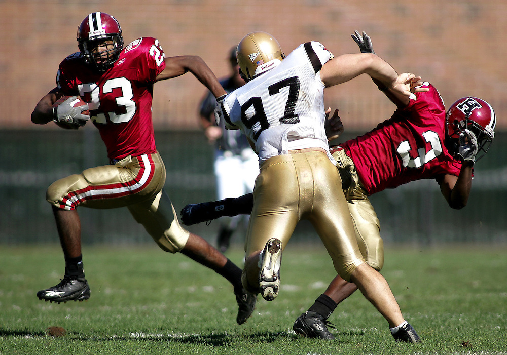 (100105-Allston, MA) Doug Hewlett, #23, of Harvard, runs the ball past Peter Morelli, #97, of Lehigh, as Morelli throws aside Daniel Tanner, #3, of Harvard in their game at Harvard Stadium.