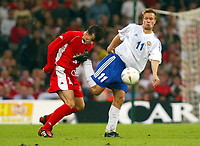 Photograph: Scott Heavey.<br />Wales v Finland. Euro 2004 Qualifier from The Millenium Stadium in Cardiff. 10.09.2003.<br />Simon Davies takes a boot to the chin from Joonas Kolkka