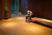 TOKYO, JAPAN, 30 SEPTEMBER - Roppongi Midtown- A man is reading a magazine seat on a  wood bench - On the left a traditional public photne. September 2012 [FR] Un homme lit un magazine dans le centre commercial Tokyo Midtown. à gauche un téléphone public