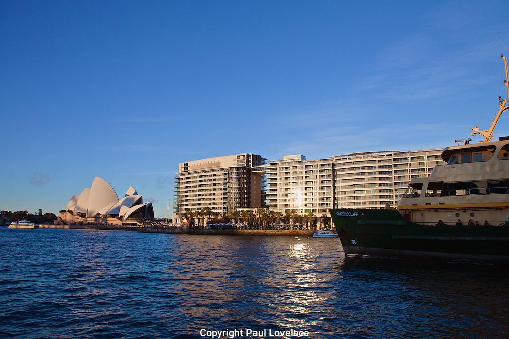 A Sydney Ferry passes the Bennelong Apartments on Sydney Harbour, Circular Quay, Sydney, Australia.