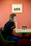 A female waitress sitting at a table at the Ty-Tan cafe along the A5 road on the 20th April 2011 in Cerrigydrudion in the United Kingdom.