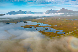 Early morning view of Rannoch Moor and A82 road  in the mist from drone, Scottish highlands, Scotland, UK