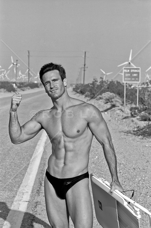 sexy man in a speedo carrying a beach chair and hitchhiking in the  California desert