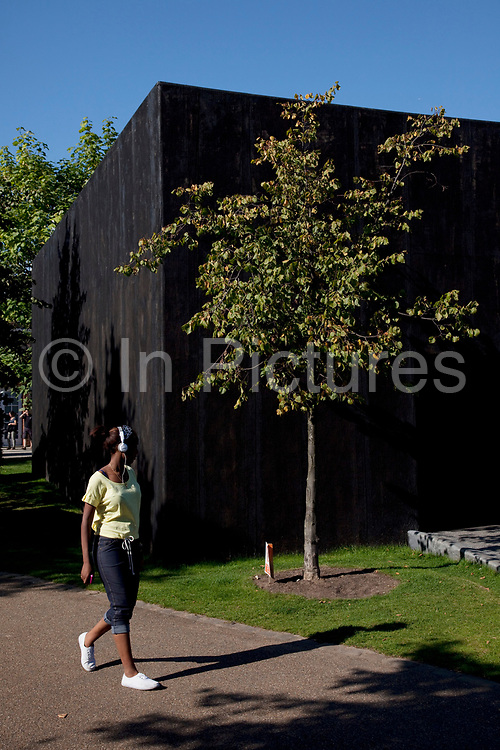 The Serpentine Gallery Pavilion 2011, designed by Peter Zumthor. People out enjoying the unseasonally hot weather as a summertime heat wave hits London and the UK in what should be Autumn. Summer prolonged in a heatwave which results in a packed Hyde Park as families and friends try to soak up the last rays of sunshine and warmth in this Indian Summer.