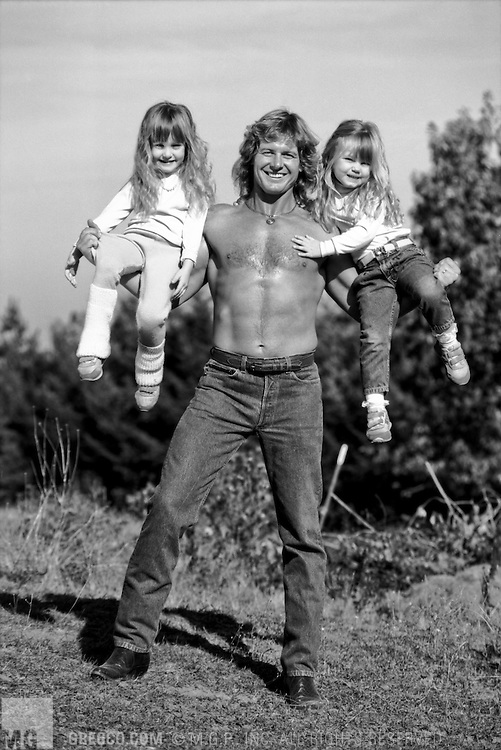 Hillsboro, OR - OCTOBER 25:  Professional wrestler Roddy Piper poses with his daughters L-R; Anastasia Shea (age 5) and Ariel Teal (age 3) at his home on October 25, 1988 in Hillsborough, Oregon.  (Photo by Michael Grecco) Image from MGPStockPhotos.com