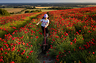 A young girl and her dog run through a field of poppies near Goodwood, West Sussex.<br /> Picture date Thursday 24th June, 2021.<br /> Picture by Christopher Ison. Contact +447544 044177 chris@christopherison.com
