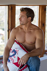 shirtless muscular tanman at home holding a decorative pillow