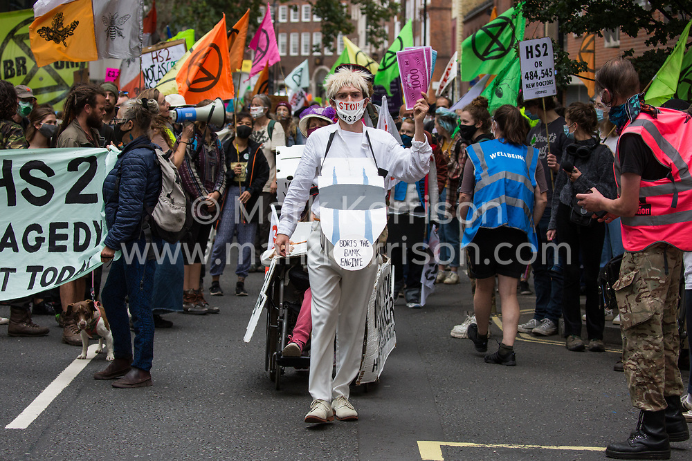 Activists from HS2 Rebellion, an umbrella campaign group comprising longstanding campaigners against the HS2 high-speed rail link as well as Extinction Rebellion activists, march with the handmade Boris the Bank Engine to a protest outside the Department for Transport on 4 September 2020 in London, United Kingdom. Activists glued themselves to the doors and pavement outside the building and sprayed fake blood around the entrance during a protest which coincided with an announcement by HS2 Ltd that construction of the controversial £106bn high-speed rail link will now commence.