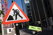 In the week that many more Londoners returned to their office workplaces after the Covid pandemic, a construction worker carries materials next to a 'Man at Work' sign in the City of London, the capital's financial district, on 8th September 2021, in London, England.