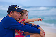A little girl in her daddy's arms points at the surf on Oahu's north shore, Hawaii
