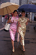 Two Chinese and European women wearing Cheongsam dresses aka qipao walk through Central, on their way to a handover party on the eve of the handover of sovereignty from Britain to China, on 30th June 1997, in Hong Kong, China. Midnight signified the end of British rule, and the transfer of legal and financial authority back to China. Hong Kong was once known as fragrant harbour or Heung Keung because of the smell of transported sandal wood.