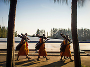 "02 JANUARY 2015 - KHLONG LUANG, PATHUM THANI, THAILAND: Buddhist monks walk through the grounds at Wat Phra Dhammakaya on their way to start the 4th annual Dhammachai Dhutanaga (a dhutanga is a ""wandering"" and translated as pilgrimage). More than 1,100 monks are participating in a 450 kilometer (280 miles) long pilgrimage, which is going through six provinces in central Thailand. The purpose of the pilgrimage is to pay homage to the Buddha, preserve Buddhist culture, welcome the new year, and ""develop virtuous Buddhist youth leaders."" Wat Phra Dhammakaya is the largest Buddhist temple in Thailand and the center of the Dhammakaya movement, a Buddhist sect founded in the 1970s.   PHOTO BY JACK KURTZ"