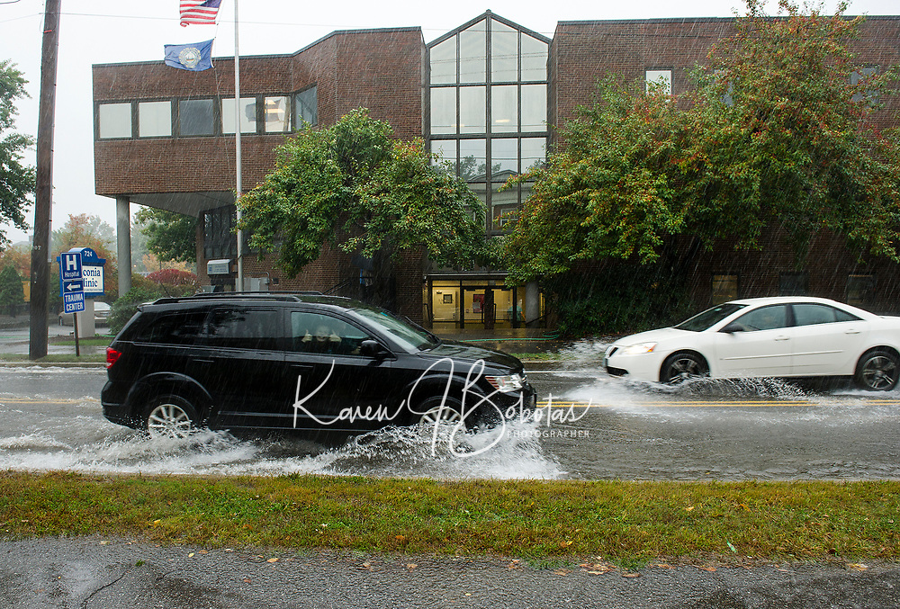 """Main Street at the Laconia Clinic with approximately 4"""" of water slowed traffic on Wednesday morning.  (Karen Bobotas/for the Laconia Daily Sun)"""