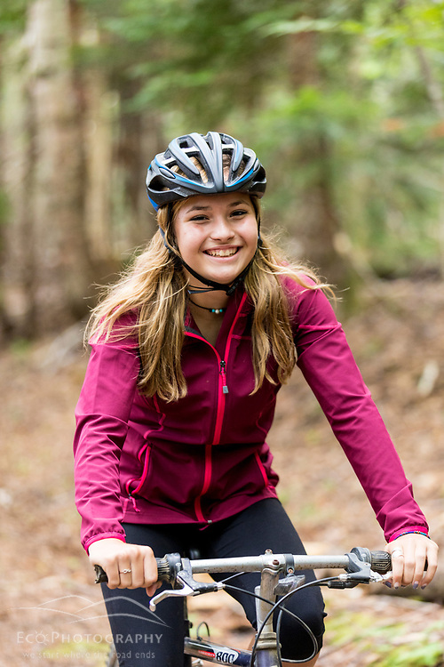 A girl rides her mountain bike on the Gardner Loop Trail, near Crater Pond in Aroostook County, Maine. Deboullie Public Reserve Land.