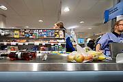 Nederland, Doesbirg, 9-3-2019Een winkel, filiaal, vestiging van supermarktketen Albert Heijn. Aan de kassa met een manlijke cassiere .Foto: Flip Franssen