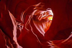 The Heart of Antelope Canyon opens above the ceiling of the canyon. Smooth curves of brick red rock form a heart formation overhead.