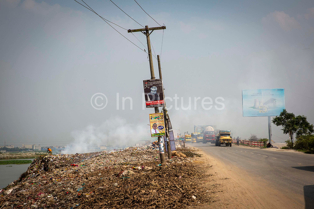 A man searches through a burning rubbish pile next to the N305 highway and the banks of the Turag river on the 1st of October 2018 in Dhaka, Bangladesh. Environmental pollution next to rivers and lakes is a common sight in Dhaka, polluting water sources that also used for washing and drinking water.