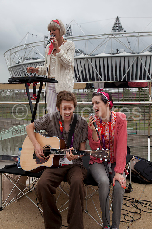 London 2012 Olympic Park in Stratford, East London. Local musicians provide some entertainment on site. This band has two singers and a guitar and performs to tha backdrop of the Olympic stadium.