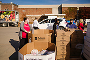 06 NOVEMBER 2020 - DES MOINES, IOWA: Volunteers ready food packages for clients during a drive through emergency food distribution at the Iowa State Fairgrounds Friday. A spokesperson for the Food Bank of Iowa said they had enough food for 1,500 families. Each family got frozen chicken legs, frozen liquid eggs, and fresh produce. There will be another emergency food distribution at the Fairgrounds on November 30. Food insecurity in the Des Moines area has skyrocketed since the start of the Coronavirus pandemic. Although unemployment rates in Iowa have fallen since a peak in June, many families that fell behind on rent are now facing eviction. The food bank spokesperson said use of the Food Bank's emergency pantries and distribution points is still increasing.    PHOTO BY JACK KURTZ