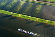 Nederland, Brabant, Gemeente Waspik, 28-10-2013; Overdiepsche polder, rivier met duwboot. In het kader van het programma 'Ruimte voor de Rivier' (bescherming tegen hoogwater door rivierverruiming), is de zomerdijk langs de Bergsche Maas van instroomgaten voorzien, terwijl de winterdijk verlaagd wordt. De uiterwaarden zijn overstroomd, bij hoogwater kan de Overdiepse polder ook overstromen. <br /> Depoldering of Overdiep Polder, farms are relocated and built on mounds. This makes it possible for the river to overflow the polder in case of heigh waters. The dikes have been excavated.<br /> luchtfoto (toeslag op standard tarieven);<br /> aerial photo (additional fee required);<br /> copyright foto/photo Siebe Swart