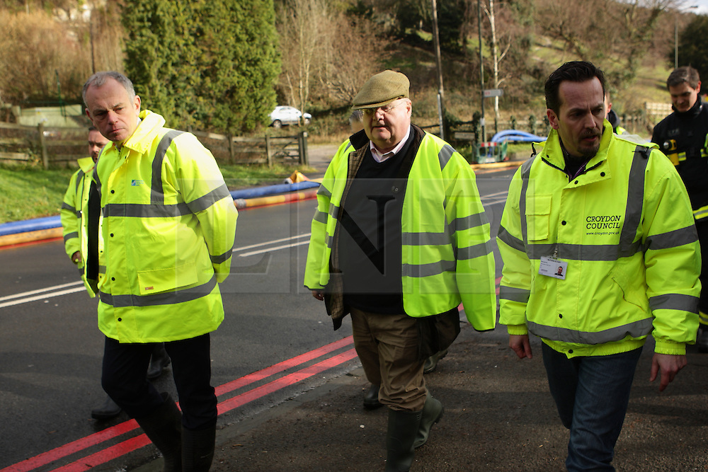 © Licenced to London News Pictures.  10/02/2014.  London UK  Eric Pickles vists the site of Kenley Water works in Godstone Road Kenley nr Purley Croydon. Flanked by members of the water works staff he toured the site and walked along the A22/ Godstone Road to see for himself the work being done <br /> Photo Credit: Presspics/LNP