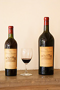 A bottle of Chateau Bouscaut 1964 and a magnum of 1962 and a glass of 2003 Chateau Bouscaut Cru Classe Cadaujac Graves Pessac Leognan Bordeaux Gironde Aquitaine France