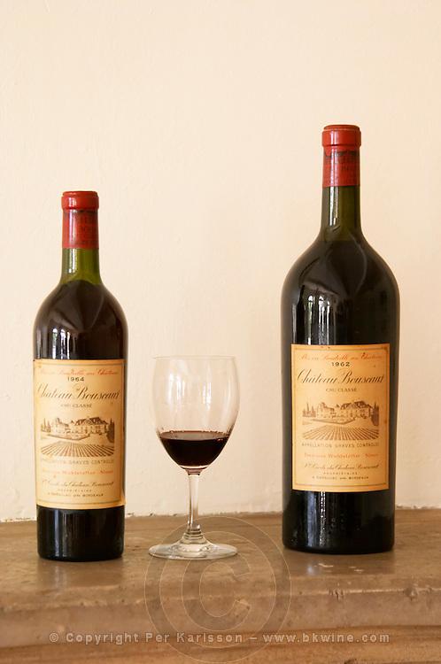 A bottle of Chateau Bouscaut 1964 and a magnum of 1962 and a glass of 2003 Chateau Bouscaut Cru Classe Cadaujac Graves Pessac Leognan Bordeaux Gironde Aquitaine France