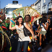A female spectator gets her photograph taken with one of the dancers in the parade. The Notting Hill Carnival has been running since 1966 and is every year attended by up to a million people. The carnival is a mix of amazing dance parades and street parties with a distinct Caribbean feel.