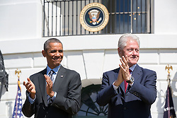 President Barack Obama and former President Bill Clinton applaud during the 20th anniversary of the AmeriCorps national service program on the South Lawn of the White House, Sept. 12, 2014. (Official White House Photo by Pete Souza)<br /> <br /> This official White House photograph is being made available only for publication by news organizations and/or for personal use printing by the subject(s) of the photograph. The photograph may not be manipulated in any way and may not be used in commercial or political materials, advertisements, emails, products, promotions that in any way suggests approval or endorsement of the President, the First Family, or the White House.