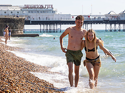 Licensed to London News Pictures. 08/09/2021. Brighton, UK. Last chance of sun. Students, Ellisabella Reynolds and Conor Kean both 21, cool off with a splash in the sea at Brighton Beach, East Sussex. Weather forecaster predict an end to the hot weather as thunderstorms are set to hit England tonight. Photo credit: Alex Lentati/LNP