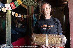 Round the World Doug Wothke holding a precious Buddhist manuscript in a private family museum in Marpha on day-6 of our Himalayan Heroes adventure riding from Muktinath to Tatopani, Nepal. Sunday, November 11, 2018. Photography ©2018 Michael Lichter.