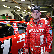 Driver Justin Allgaier is seen by his car during the  56th Annual NASCAR Daytona 500 practice session at Daytona International Speedway on Wednesday, February 19, 2014 in Daytona Beach, Florida.  (AP Photo/Alex Menendez)