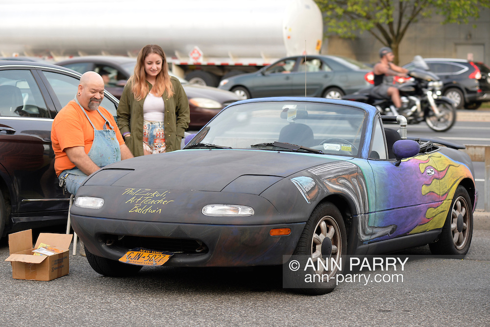 Bellmore, New York, USA. May 29, 2015. PHIL ZIRKULI, a Baldwin Art Teacher, free-hand draws colorful designs with chalk paint on his black 1992 Mazda Convertible at the Friday Night Car Show held at the Bellmore Long Island Railroad Station Parking Lot. Zirkuli explained he decorates his car to draw attention to the importance of art education. Hundreds of classic, antique, and custom cars are generally on view at the free weekly show, sponsored by the Chamber of Commerce of the Bellmores, from May to early October.