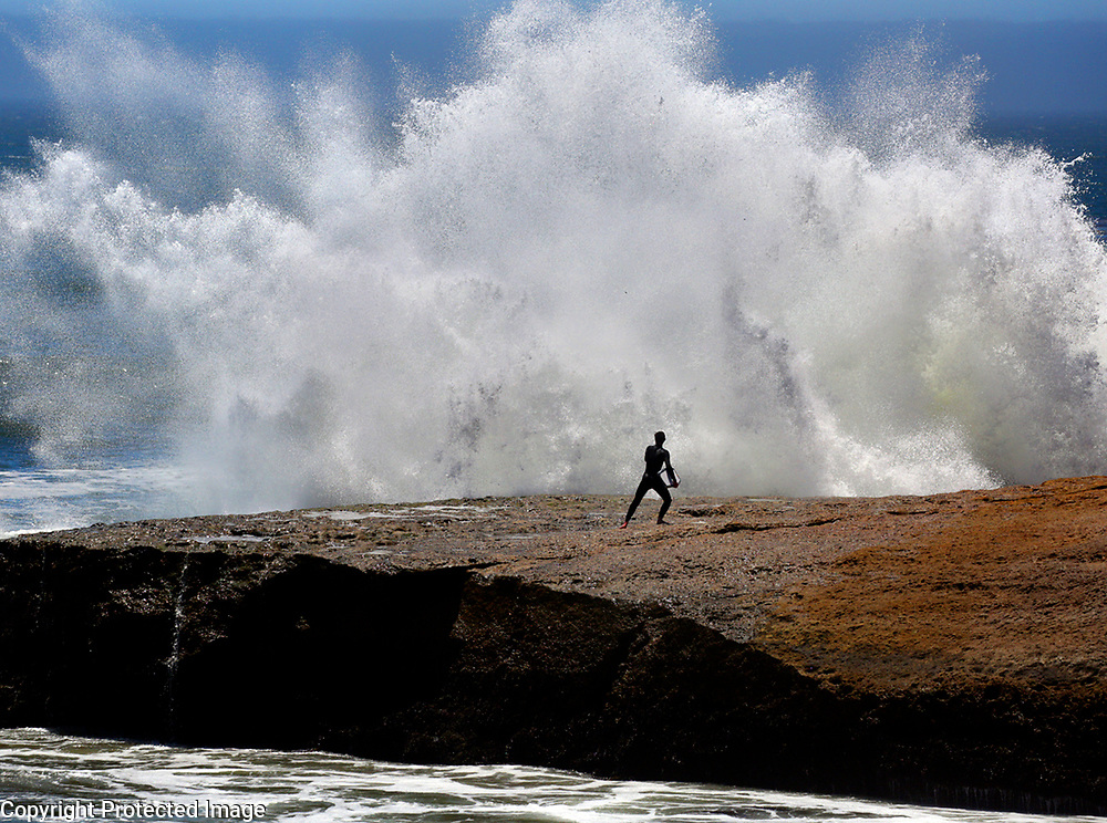 A boogie boarder scurries away from an incoming wave on the rocks off of Sunny Cove at the end of 17th Avenue in Santa Cruz, California on Tuesday June 12, 2018. A south-southwest brought in waves in excess of 7 feet to some local breaks.<br /> Photo by Shmuel Thaler <br /> shmuel_thaler@yahoo.com www.shmuelthaler.com