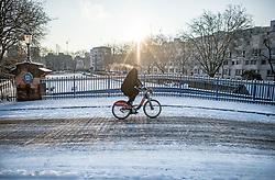 © Licensed to London News Pictures. 28/02/2018. London, UK. A man rides a bike through picturesque scenes at sunrise in Little Venice, West London following heavy snowfall last night. Large parts of the UK are experiencing disruption as 'Storm Emma' hits, following Russian a cold front earlier in the week named 'The Beast From The East'. Photo credit: Ben Cawthra/LNP