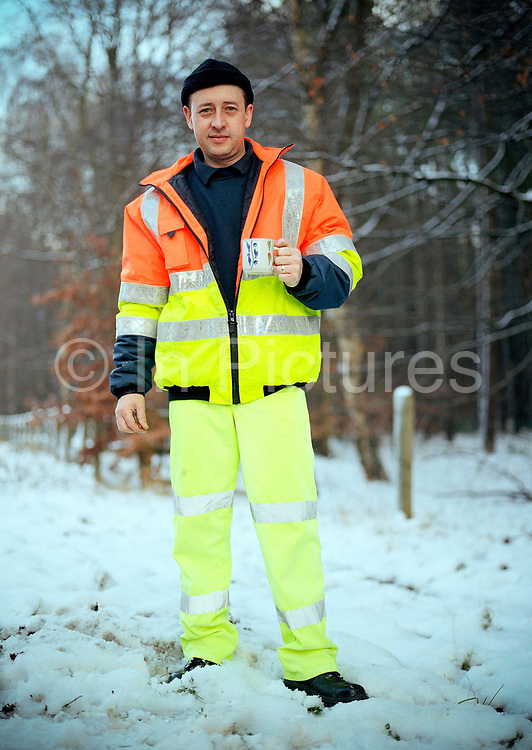 On a wintry morning, a waste disposal worker enjoys a hot drink at a roadside burger van on the 5th January 2010 in Thetford Forest in the United kingdom.