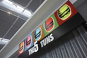 Looking upwards to 5 Tuns retail sign in landside Departures area newly-opened London Heathrow Airport's Terminal 5 building.