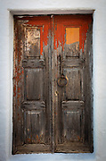 Old door in the town of Chora on Patmos island in Greece. Patmos is a small Greek island in the Aegean Sea. One of the northernmost islands of the Dodecanese complex, it has a population of 2,998 and an area of 34.05 km2 (13.15 sq mi). The Municipality of Patmos, which includes the offshore islands of Arkoi, Marathos, and several uninhabited islets, has a total population of 3,047 and a combined land area of 45.039 square kilometres (17.390 sq mi). It is part of the Kalymnos regional unit.<br /> <br /> Patmos' main communities are Chora (the capital city), and Skala, the only commercial port. Other settlements are Grikou and Kampos. The churches and communities on Patmos are of the Eastern Orthodox tradition. In 1999, the island's historic center Chora, along with the Monastery of Saint John the Theologian and the Cave of the Apocalypse, were declared World Heritage Sites by UNESCO. The monastery was founded by Saint Christodulos. Patmos is also home to the Patmian School, a notable Greek seminary.