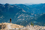 Hiker looking south from the top of Mount Aeneas, the highest peak in the Flathead Valley, into Jewel Basin, part of the Flathead National Forest in NW Montana.